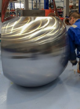 An engineer performs a visual inspection of hard facing on a re-ground 30� ball.